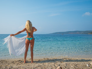 Woman in sarong standing on the beach