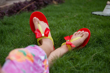 only feet of a girl wearing red slippers and sitting in grass