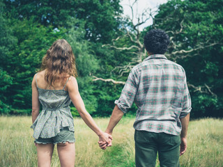 Young couple holding hands in meadow