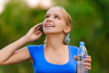 Smiling teenager girl with bottle talking on phone