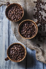 Three Cups of Coffee Beans on a Wooden Table with Burlap; From Above
