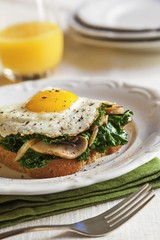Kale and Mushrooms Topped with a Fried Egg on a Piece of Toast; Glass of Orange Juice