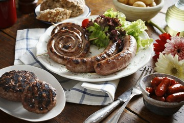 A plate of barbecued sausage spirals and sausages
