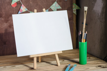 Art supplies. Brushes, easel, paper. Place for your text. Mock up photography.