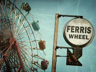 aged and worn vintage photo of ferris wheel and sign