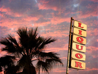 aged and worn vintage photo of liquor sign with palm tree