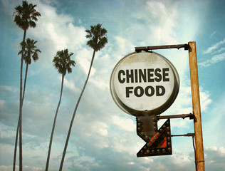 aged and worn vintage photo of chinese food sign and palm trees