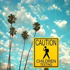 Aged and worn vintage photo of caution road sign with child texting