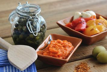 Peperonipaste - Paprikamousse auf Holztisch mit Kapern und Kochlöffel