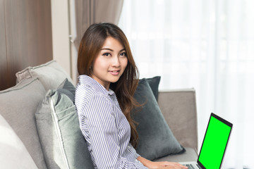 Beautiful young asian woman using laptop on sofa in the living room.
