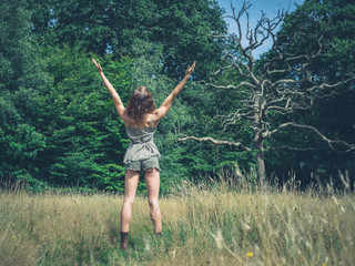 Woman raising her arms in forest
