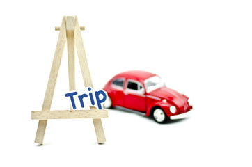 KUALA LUMPUR, MALAYSIA 17 AUGUST 2015 : image with word trip on tripod stand made from wood and Volkswagon Beetle collectible model car