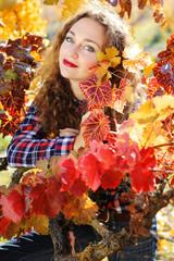 Beautiful young woman in autumn grape vineyard