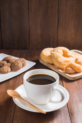 Coffee cup, donuts, cookie on wooden background