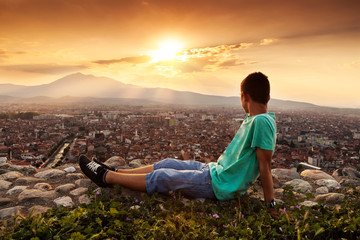 young relaxing boy looking to the city in the sunset atmosphere