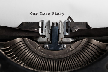 Our love story slogan written by a typewriter on a sheet of a paper