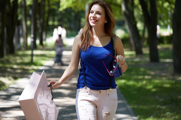 beautiful girl in the park with shopping bag