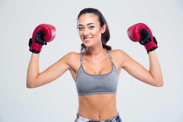 Fitness woman standing with boxing gloves in victory pose