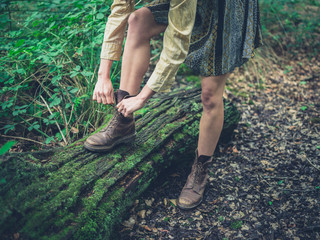 Woman tying her shoes in the forest