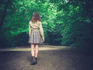 Young woman walking on road in forest