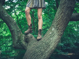 Young woman standing in a tree