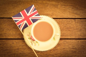 A cup of tea and a union jack on a wooden table