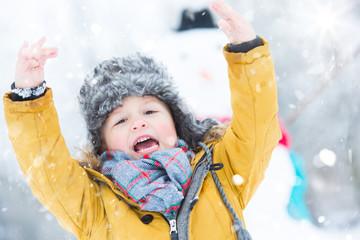 kleiner junge jubelt im schnee