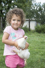 Little girl in the summer in the garden holding a chicken.