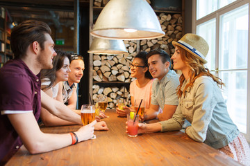 happy friends with drinks talking at bar or pub