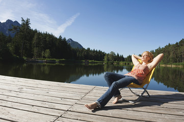 Italy,South Tyrol,Woman sunbathing on jetty by lake
