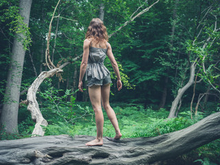 Barefoot woman standing on a fallen tree in the forest