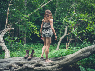 Woman taking off her boots in forest