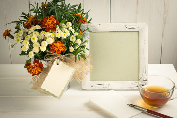 Retro photo frame and old pen with sheet paper and tagetes bouqu