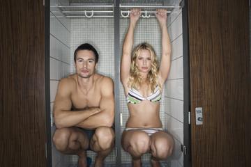Couple sitting in locker,man crossing arms