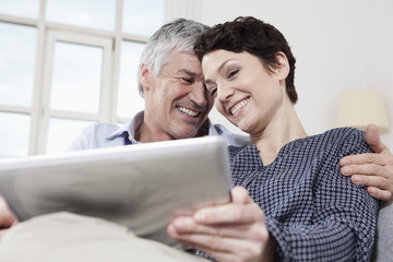 Germany,Bavaria,Munich,Couple using digital tablet at home,smiling