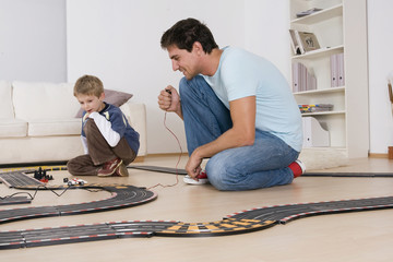 Father and son (6-7) playing with toy racetrack