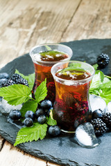 Cold black tea with berries and ice, selective focus