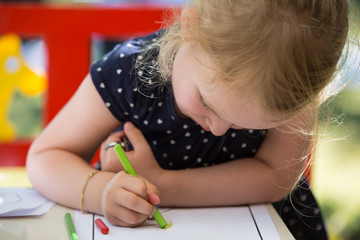 Young blond girl coloring a page with oil pastel crayons