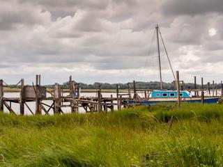 Skipool Creek, Thornton Cleveleys, Lancashire, UK. August 11th 2015. Wooden piers at low tide at Skipool Creek, Lancashire, uk.