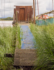 Skipool Creek, Thornton Cleveleys, Lancashire, UK. August 11th 2015. The old wooden huts at low tide at Skipool Creek, Lancashire, uk.