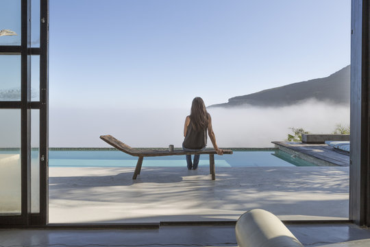 Woman sitting on a lounge next to pool