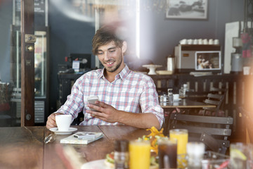 Smiling young man in a cafe looking on cell phone