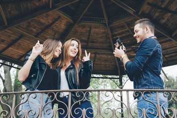 Spain, Barcelona, young man taking a photo of his two female friends