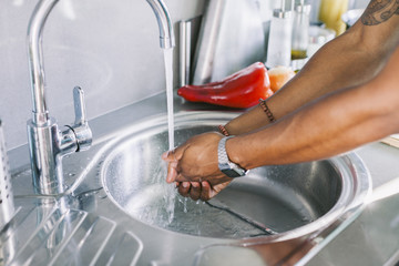 Man washing his hands in the kitchen