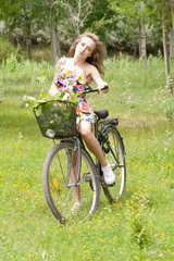Teenage girl with her bicycle in forest