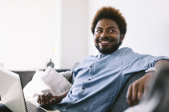 Young A man sitting on couch, using laptop