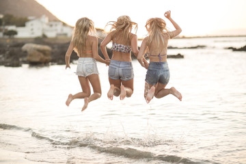 Three young women jumping on a beach in waves