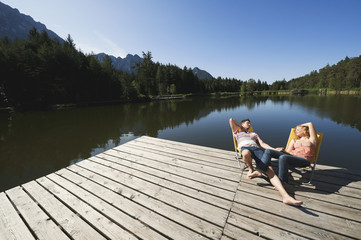 Italy,South Tyrol,Couple sunbathing in chairs on jetty