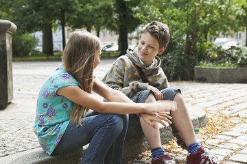 Germany,Berlin,Boy and girl sitting on curbstone