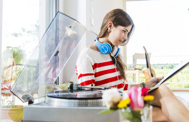 Young woman at home looking at records